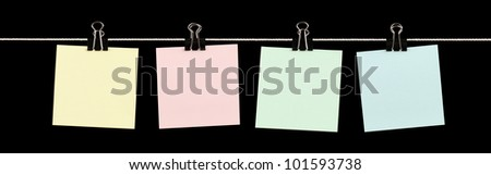 Four blank sticky notes of various colours held on a string with binder clips isolated on black.