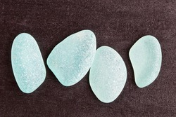 four blue glass pieces polished by the sea closeup on black background