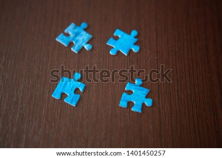 four blue puzzle pieces on wooden background