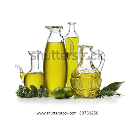 Four bottles of olive oil with two olives and spices on white background