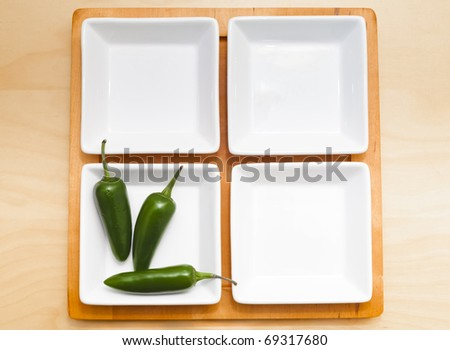 Four bowls of which one contains chili peppers