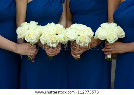 four bridesmaids in blue dresses holding white rose bouquets
