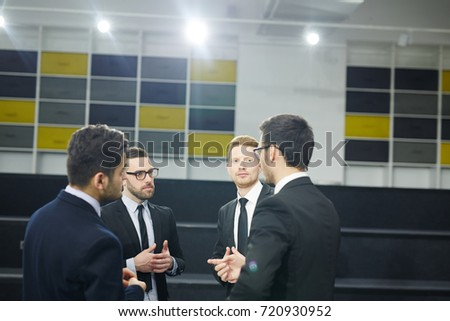 Four brokers in formalwear sharing their ideas and opinions about reports of conference
