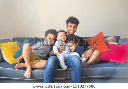 Four brothers sitting on the sofa, hugging