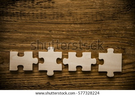 Four brown pieces of puzzle lie on wooden table background. empty copy space for inscription or objects. #577328224