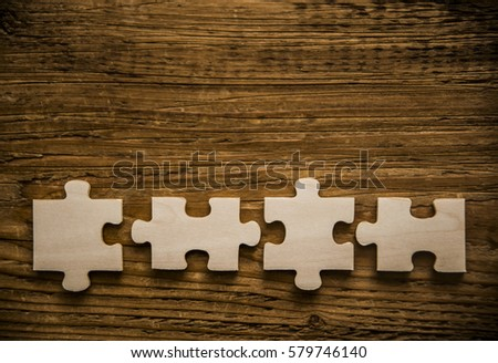 Four brown pieces of puzzle lie on wooden table background. empty copy space for inscription or objects. #579746140