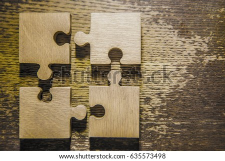 Four brown pieces of puzzle lie on wooden table background. empty copy space for inscription or objects. #635573498