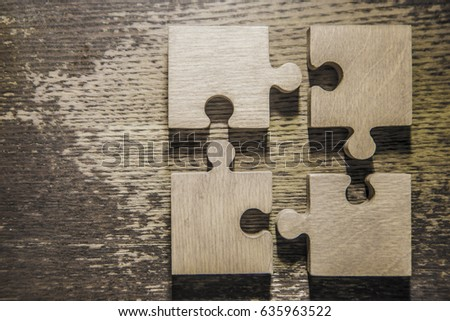 Four brown pieces of puzzle lie on wooden table background. empty copy space for inscription or objects. #635963522