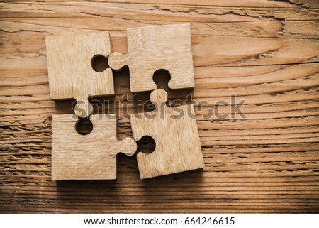 Four brown pieces of puzzle lie on wooden table background. empty copy space for inscription or objects. #664246615