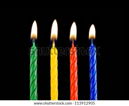 Four burning candles on black background