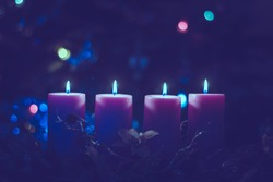 four burning candles with tradition festive cristian atmosphere, magic dramatic purple tone