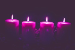 four burning candles with traditional festive cristian atmosphere full of light and magic, purple tone, copy space