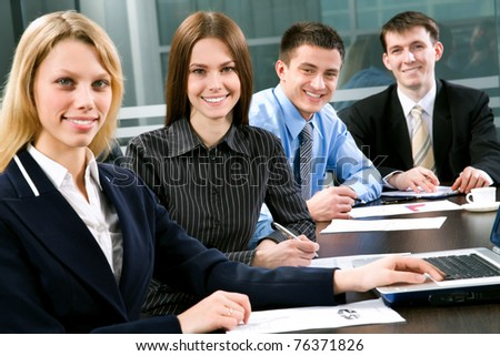 Four business colleagues sitting around table and working together, looking at camera, smiling
