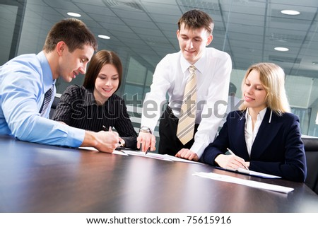Four business colleagues working together, smiling