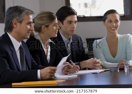 Four business executives sitting at a conference table in a conference room