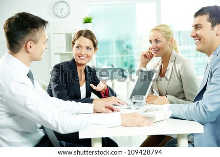 Four business partners sitting in office and interacting at meeting