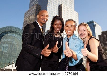 Four business people giving thumbs up. Horizontally framed shot.