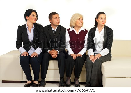 Four business people sitting in a row on sofa and looking in right part of image with different facial expressions on their faces