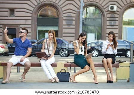 Four business people sitting on a bench in the summer city