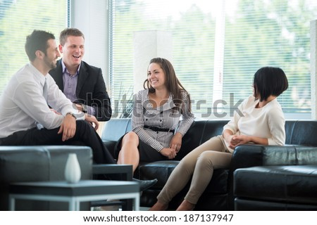 Four business people talking on a break in modern environment