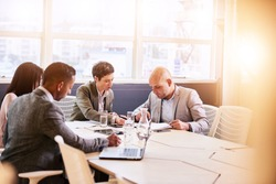 Four business professionals conducting a meeting in a bright modern conference room with a large windown and an abundance of natural light, while making use of technology to optimise efficiency.
