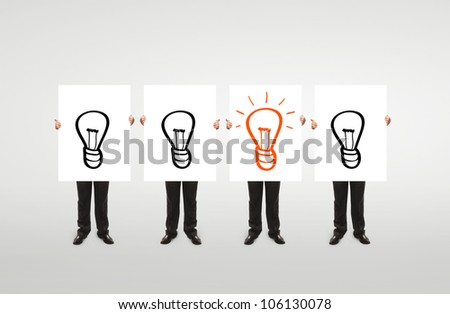 """four  businessman holding a white board with """"idea"""" symbol"""