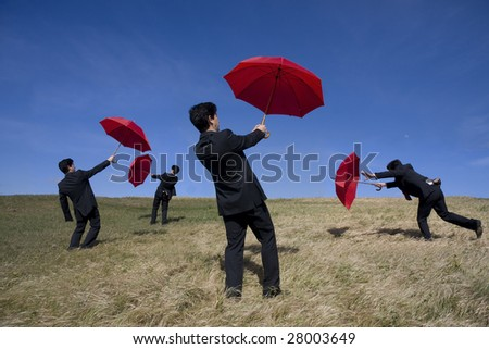 Four businessman with red umbrellas on the nature