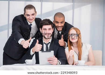Four businessmen looking at a tablet. Four confident successful businessmen at a meeting while sitting at a table discussing business case in the office showing thumbs up #229348093