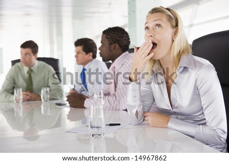 Four businesspeople in boardroom with one businesswoman yawning