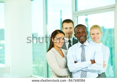Four businesspeople looking at camera and smiling in office