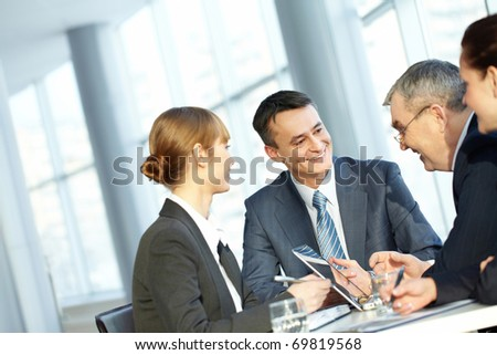 Four businesspeople sitting at table, and interacting