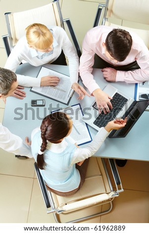 Four businesswomen communicating and looking at the laptop screen
