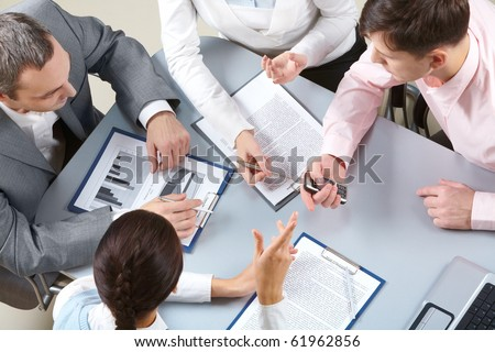 Four businesswomen sitting at table examining some documents