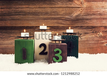 four candles on blocks with the numbers 1 to 4 for advent , concepts for advent