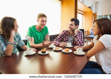 Four casual students having a cup of coffee chatting in college canteen