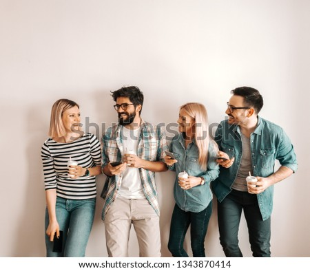 Four Caucasian business people drinking coffee to go, chatting, laughing and holding coffee to go while standing against the wall.