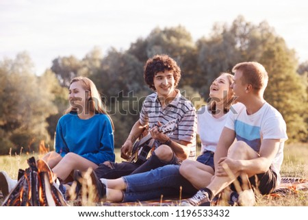 Four Caucasian female and male friends laugh joyfully together, pose near campfire, sings song on acoustic guitar, sing popular songs, enjoy recreation time, happy to meet after long departure #1196533432