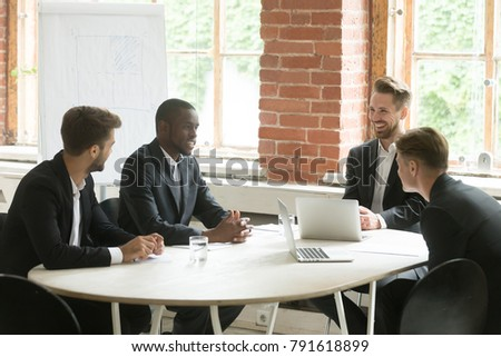 Four cheerful diverse businessmen talking laughing at meeting table, smiling satisfied multiracial executive group or partners team discussing new ideas or good work results in office together