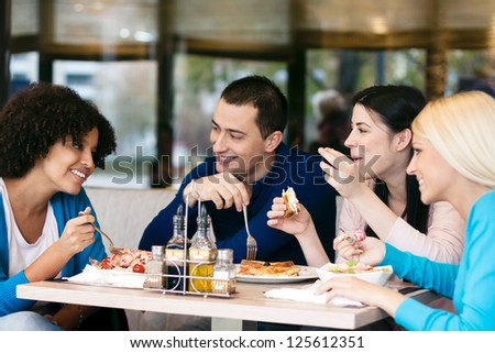 Shutterstock Four cheerful friends chatting while lunch in restaurant