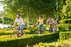 Four cheerful friends cycling outside. Group of young happy persons riding bicycles outdoors. Summer leisure with bicycles.