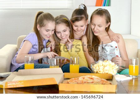 Four cheerful girls relaxing at home together