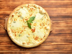 Four cheese pizza quattro fromaggi with basil leaf on a rustic wooden board background