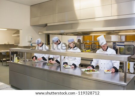 Four Chef's preparing plates in the kitchen - stock photo