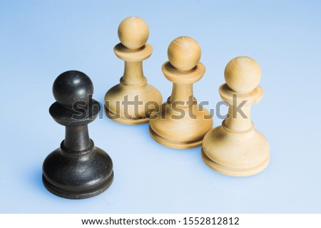 four chess pieces in front of a light blue coloured background. one black piece and three white pieces in a row.