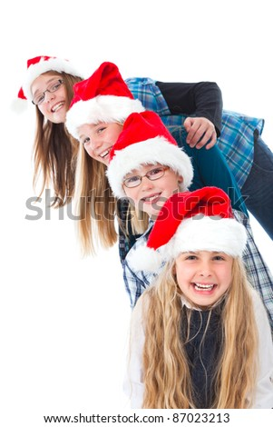 four children with christmas hats sidewise on white laughing