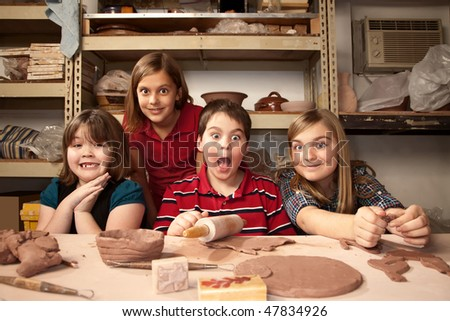 Four children working on crafts in a clay studio with funny expressions
