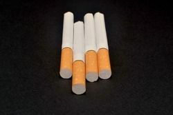 four cigarettes with orange filters on a black background
