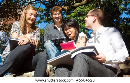 Four college students having fun on the steps of the college grounds