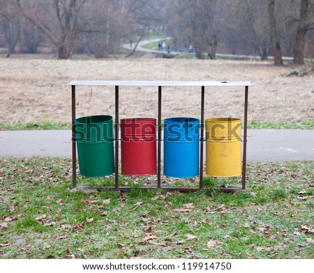 Four color trash cans (garbage bin) in the park beside the walk way