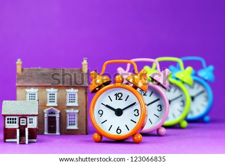 Four colored alarm clocks next to two houses a small and medium houses asking the question is it time to wake up to the housing market!